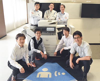 seven members of the development team behind the MX-6070N/5070N digital full-color MFPs